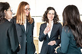 Cheerful female colleagues talking in office