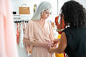 Female shop seller helping woman to try on new dress