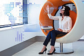Businesswoman playing VR game and virtual statistic graphics