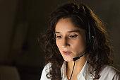 Female call center operator in dark office