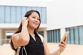 Smiling young woman listening music via smartphone