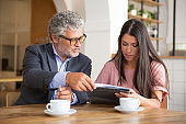 Mature legal advisor helping young customer to complete document