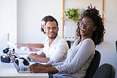 Cheerful colleagues laughing during work