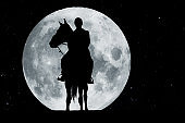 Silhouette of a rider on a horse before full moon