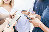 Group of friends meeting outside and using smartphones