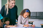 Cheerful female school teacher watching girls doing their task