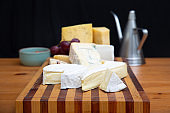 Various cheeses laying on wooden board