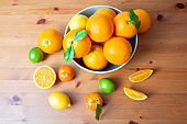 Top view of big bowl with fresh oranges standing on wooden desk