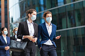 Female professionals wearing office suits and masks