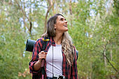 Beautiful young woman hiking in mountains with backpack