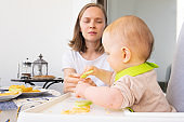 Focused mom giving slice of fresh vegetable to baby