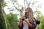 Pretty blonde woman standing in forest with camera