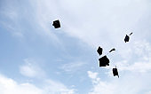 Graduation hat Thrown in the Air with blue sky  background.