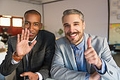 Two smiling businessmen waving and showing thumb up