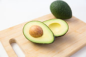 Halved and whole avocado fruit on wooden chopping board