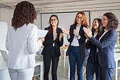 Cheerful colleagues applauding after presentation in office