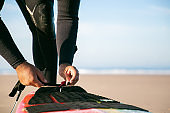Hands of surfer in wetsuit tying surfboard to his ankle