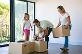 Happy family with kids near carton boxes standing in living room