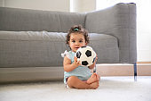 Happy black curly haired baby girl sitting on floor at home