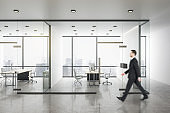 Young businessman walking in modern office