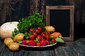 plate with fresh seasonal vegetables and black background for text