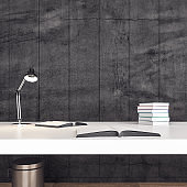 Minimalistic office desk with books on table.
