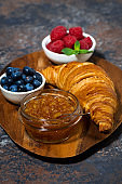 croissant, jam and berries on a wooden board