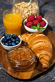 croissant, jam and berries on a wooden board, top view