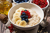 homemade oatmeal with berries on wooden background, closeup