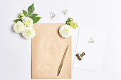 workplace concept. flowers dahlias on a white background. gold writing materials and notepad made kraft paper. simple flat lay compositions, mockup