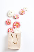 creative shopping concept, simple flat layout. craft package and Aster flowers on a white background, top view, vertical frame