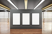 Three blank poster on gray wall in modern spacious hall