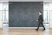 Businessman walking in modern empty office hall