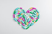 Abstract color capsule medication in form heart.