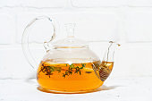 flavored black tea with thyme in a glass pot