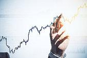 Businessman hand drawing business stock analytics