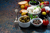 mozzarella, ingredients for the salad and bread on dark background, closeup