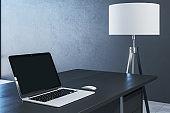 Blank laptop screen on table in office.