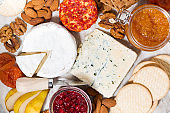 assortment of gourmet cheeses and snacks on board, top view closeup