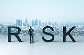 Businessman standing near risk text