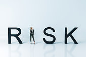 Thinking businesswoman standing near risk text.
