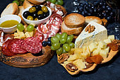 cheese platter on a wooden board, bread, fruit and cold cuts on dark background, closeup