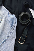a set of jeans trousers, black shirts and a leather belt close-up. online shopping concept. vertical frame