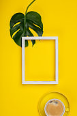 Creative flat lay with cup of coffee, tropical plant and white frame for your text