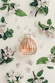Beautiful perfume bottles and spring flowers on off white background