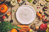 Fresh garden carrots, pumpkins, onions, apples and spices on rustic background with wooden tray in center, top view, copy space
