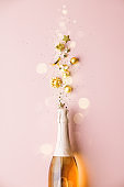 Flat lay of Celebration. Champagne bottle and golden decoration on pink background
