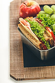Lunch box with sandwich and fruits on chalk board