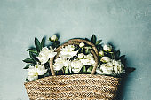 Flat-lay of Beautiful peony flowers in straw bag over blue rustic background