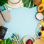 Straw hat, camera, bag, summer shoes, sunglasses, shells, tropical leaves and fruits over yellow background